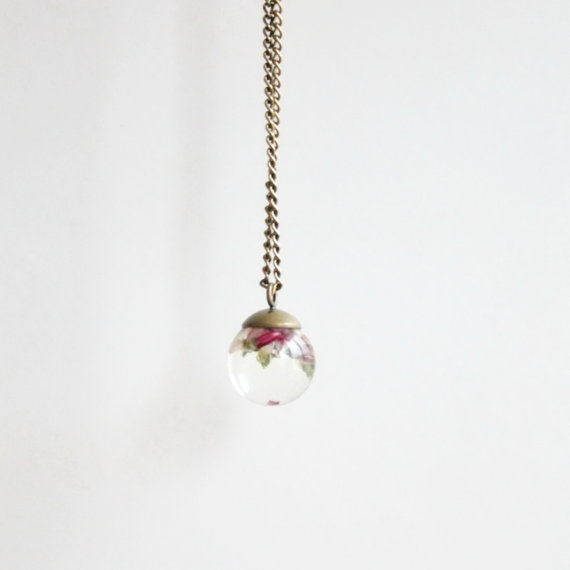 Small spherical transparent pendant with tiny pink flowers
