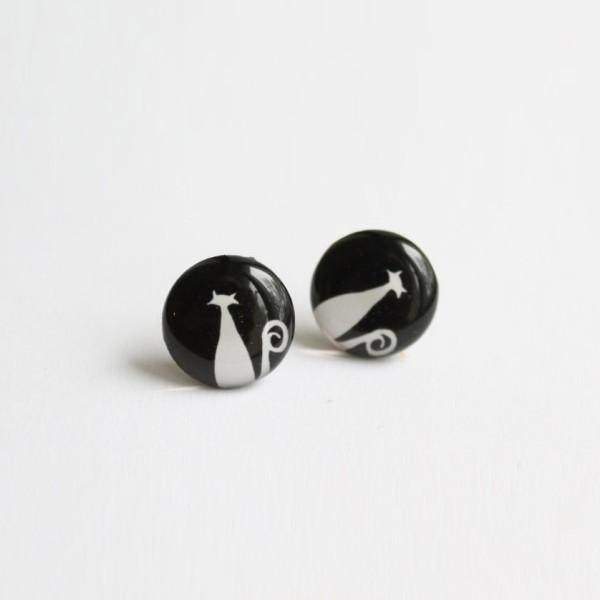 Cat stud earrings, black background, white cat