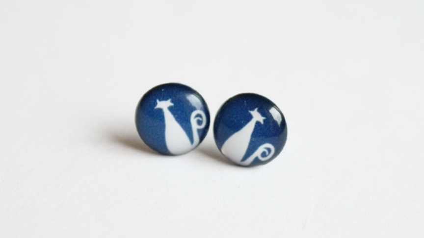 Cat stud earrings with navy blue background