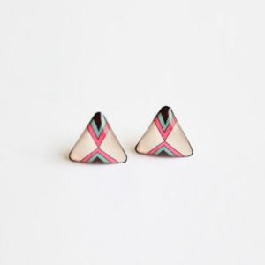 Beige triangle stud earrings on a hand