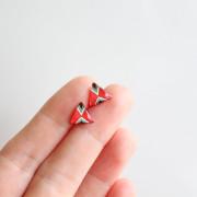 red triangular studs in hand